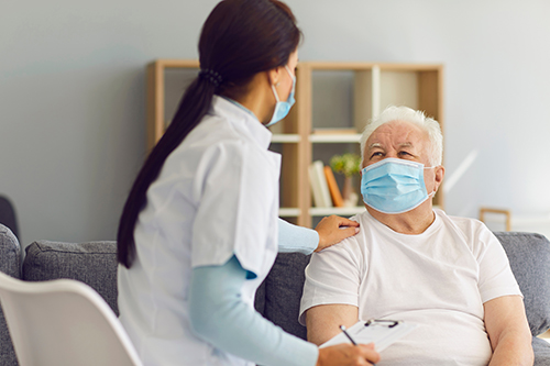 Stock photo of a nurse with a patient. Both are masked.